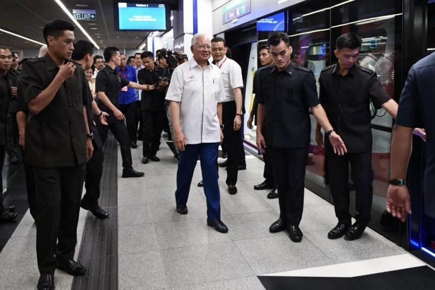 Malaysia's Prime Minister Najib Razak (centre) walks along the platform before boarding a Malaysia Mass Rapid Transit (MRT) train during the official launch of the MRT Sungai Buloh-Kajang (SBK) rail line in Kuala Lumpur on July 17, 2017.