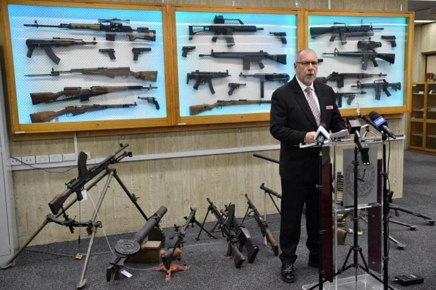 Detective Chief Inspector Wayne Hoffman of the New South Wales Police speaks to the media at a press conference at their headquarters in Sydney on on August 8, 2017, as guns previously seized from criminals are seen behind him.
