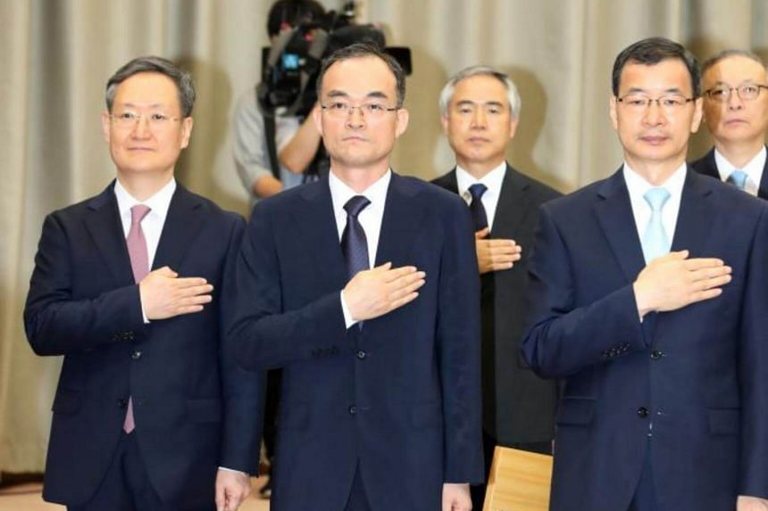 New Prosecutor General Moon Moo-il (centre-left) salutes the national flag during an inauguration ceremony at the Seoul High Prosecutors Office in Seoul, South Korea on July 25, 2017.