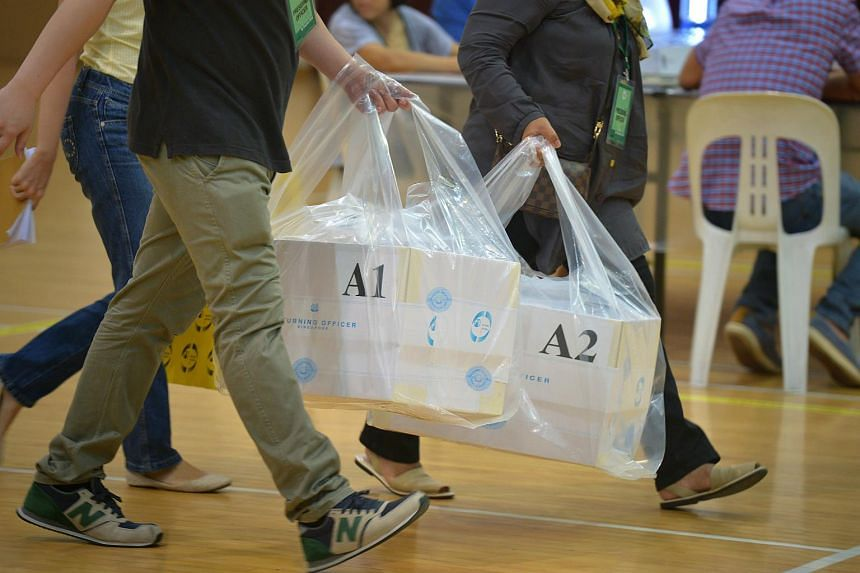 Ballot boxes being brought into the school hall at the Bukit Batok Secondary School Counting Centre after voting closed on Polling Day on May 7, 2016.