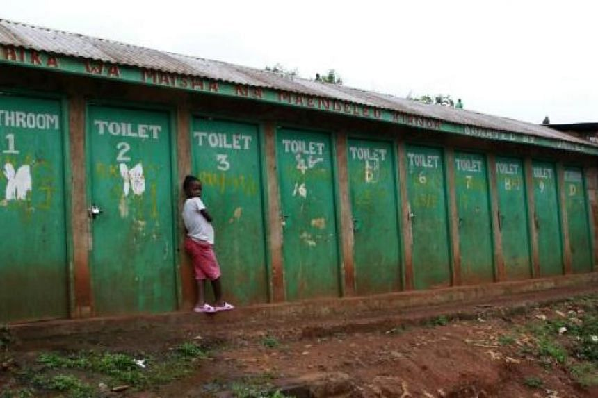 A girl waits to use a public toilet in the sprawling Kibera slum, home to about 1 million people in Kenya's capital Nairobi.