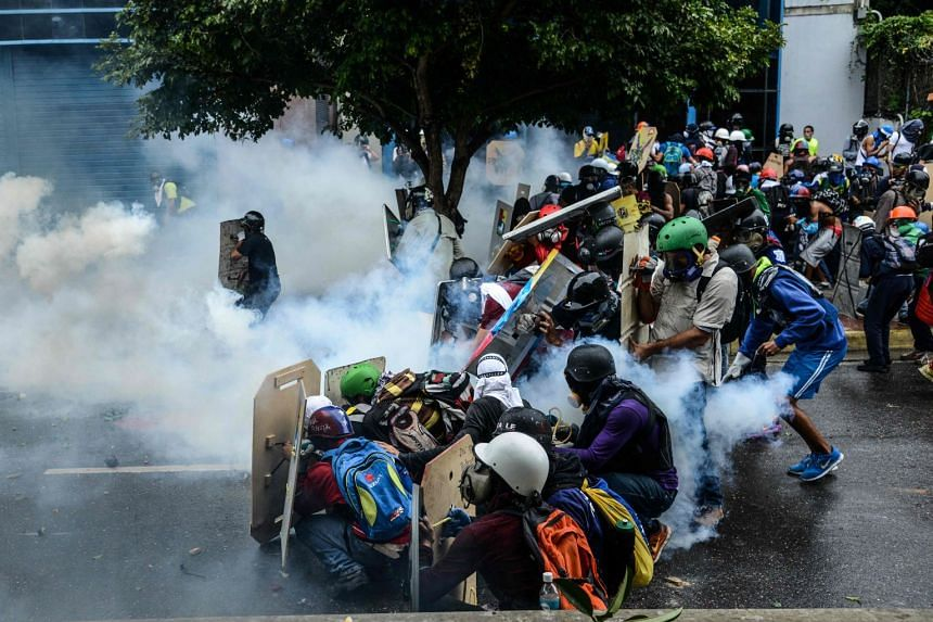 Opposition demonstrators and riot police clash during a protest against the government of President Nicolas Maduro in Caracas on June 7, 2017.