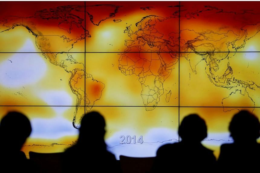 Participants looks at a screen projecting a world map with climate anomalies during the World Climate Change Conference 2015.