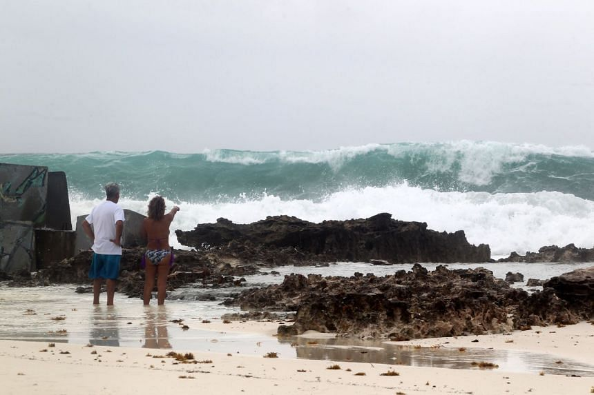 A couple observes strong waves due to Franklin's influence in Cancun, Mexico.