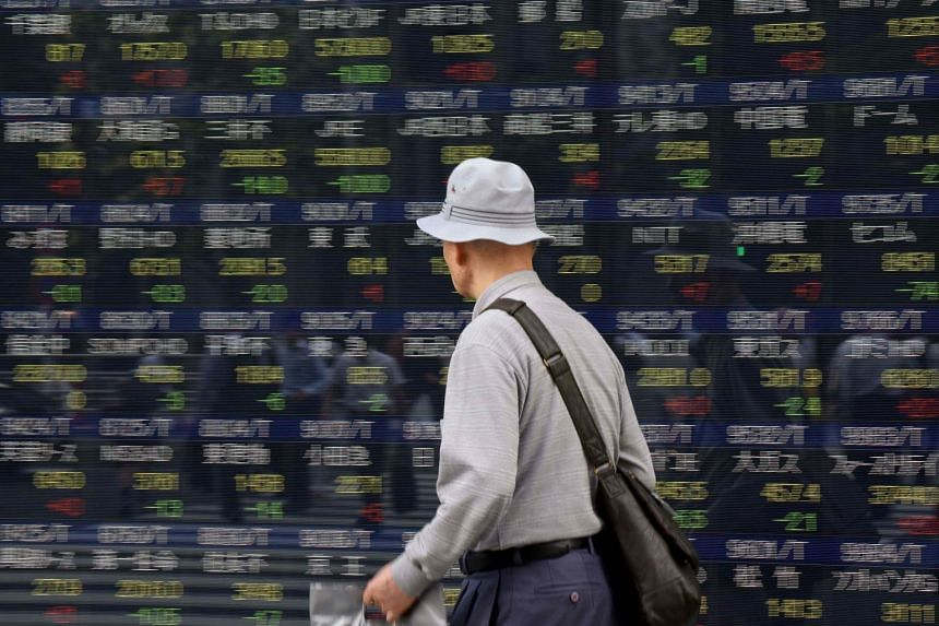 A man walks in front of a stock quotation board of the Tokyo Stock Exchange in front of a securities company in Tokyo.