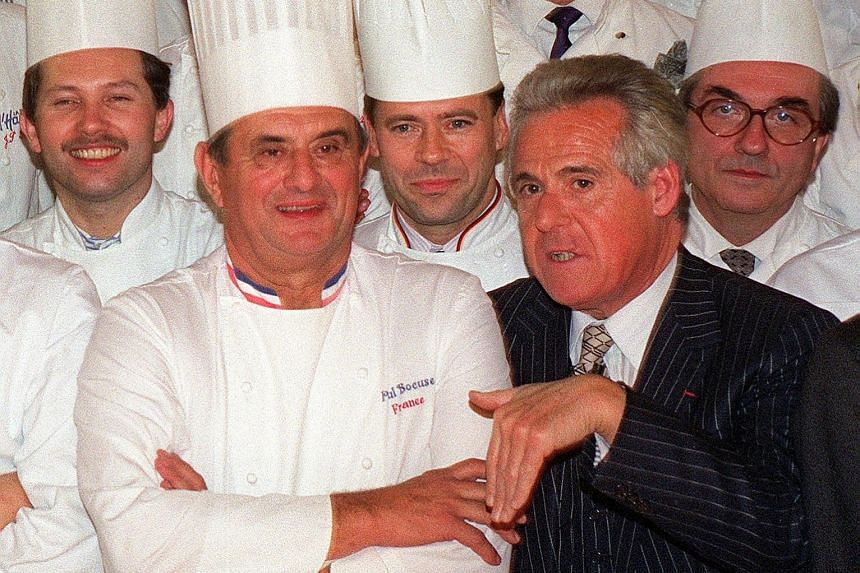 French gastronomy critic Christian Millau (in suit) with French chef Paul Bocuse (front, left) and other famous French chefs in Paris in 1989.