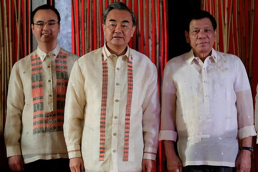 """Philippine President Rodrigo Duterte with his Foreign Secretary Alan Cayetano (far left) and Chinese Foreign Minister Wang Yi. Mr Cayetano said China set aside its insistence on a """"non-legally binding"""" code of conduct on maritime disputes in the Sout"""