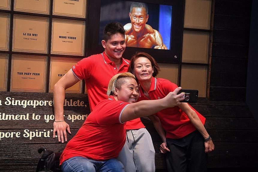 Para-swimmer Theresa Goh taking a selfie with fellow Hall of Fame inductees Joseph Schooling and Laurentia Tan in front of the Hall of Fame wall at the Singapore Sports Hub.