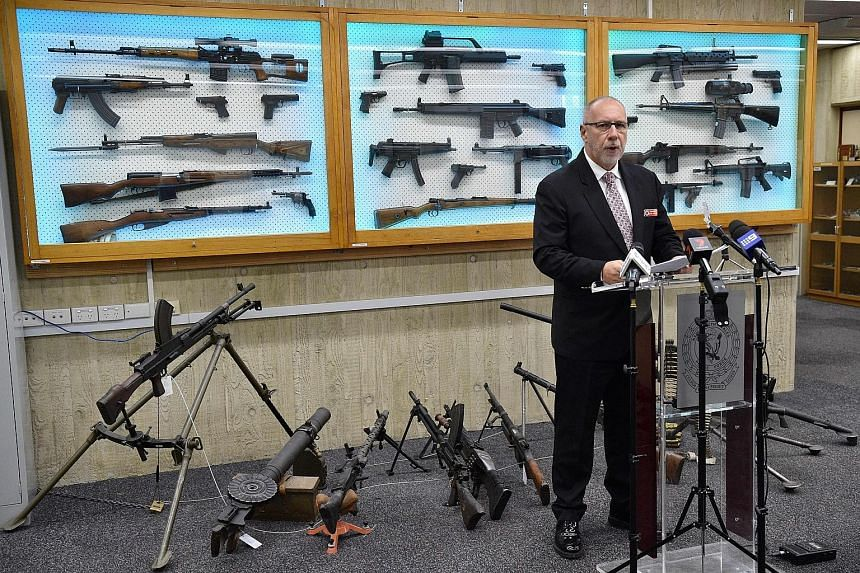 Detective Chief Inspector Wayne Hoffman of the New South Wales Police speaking to reporters yesterday with guns seized from criminals displayed behind him.