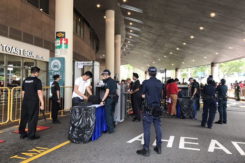 Members of the public having their bags checked by security personnel at the Esplanade, ahead of the National Day Parade on Aug 9, 2017.