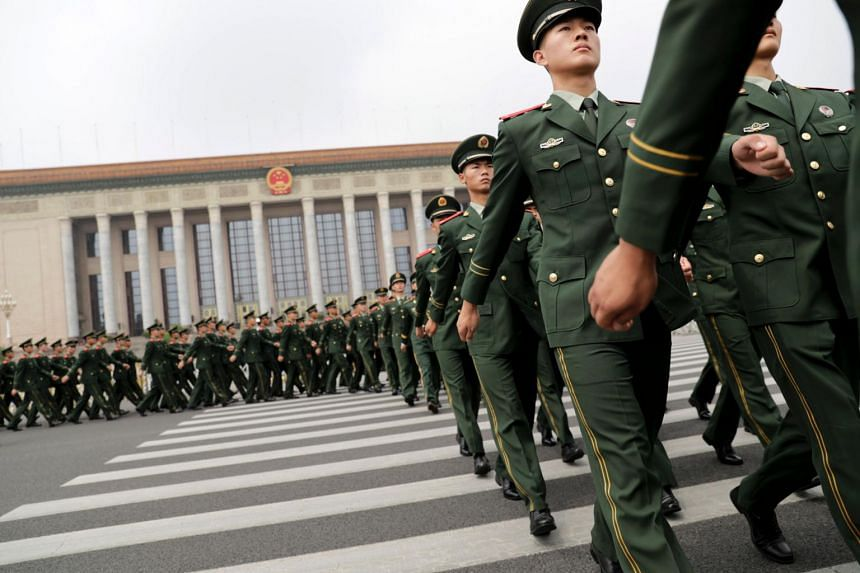 Chinese paramilitary policemen march outside the Great Hall of the People after attending a ceremony to commemorate the 90th anniversary of the founding of the People's Liberation Army, in Beijing on Aug 1, 2017.