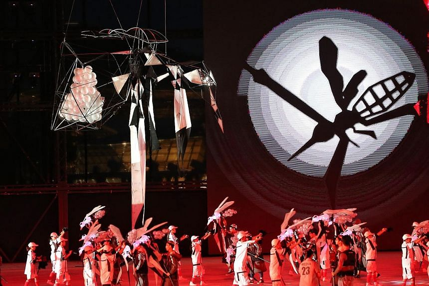 """Mosquito puppeteers and mosquito fighters entertaining the audience during the Mozzie Wipeout segment of the show's first act, Living Together. The audience was encouraged to clap in rhythm to kill the gigantic """"mosquitoes""""."""