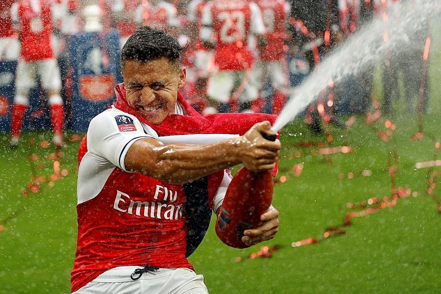 Alexis Sanchez celebrating Arsenal's FA Cup triumph last May. He will not be available for the first two league games of the season, having suffered an abdominal strain. The forward, whose contract expires next year, could move before the transfer wi