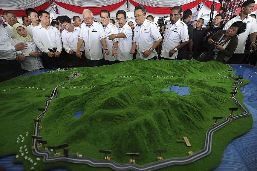 """Malaysian Prime Minister Najib Razak and China's State Councillor Wang Yong (front row, third from left) viewing a model of the East Coast Rail Link in Kuantan yesterday. Mr Najib described the rail link as a """"high-impact project that will seamlessly"""