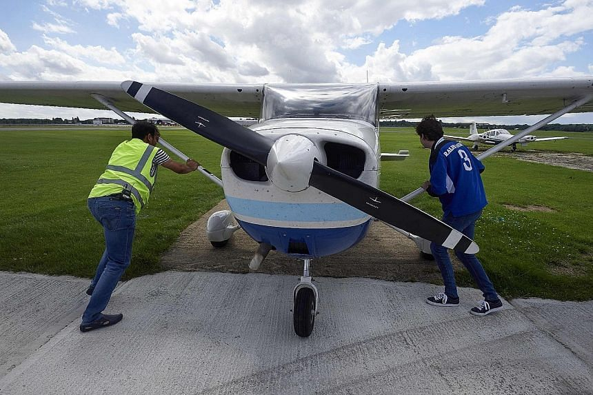 Passenger Adam Nicholas helping pilot Somasekhara Pemmiredy (left) to park the Cessna 172 plane after a Wingly flight over London, at the London North Weald airfield on Aug 1.
