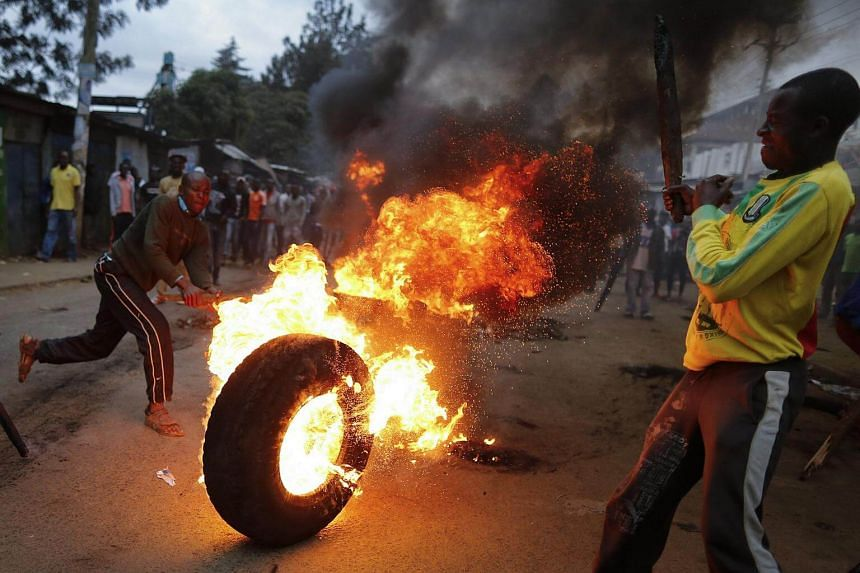 Supporters of the opposition leader Raila Odinga rolls a burning tire down the hill as they join others to protest after Odinga announced that he rejects the provisional result of the presidential election announced by the electoral body.