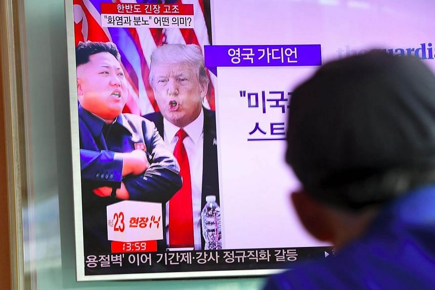 A man watches a television news programme showing US President Donald Trump (centre) and North Korean leader Kim Jong Un at a railway station in Seoul on Aug 9, 2017.