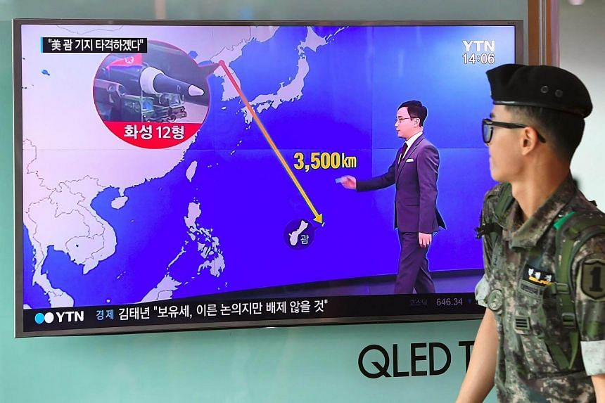 A South Korean soldier walks past a television screen showing a graphic of the distance between North Korea and Guam at a railway station in Seoul on Aug 9, 2017.