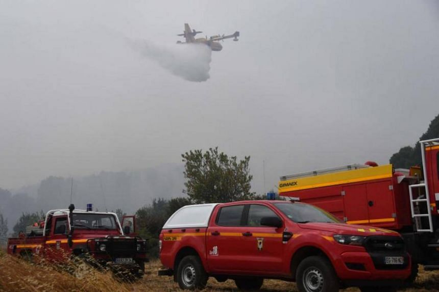 A Canadair firefighting aircraft drops water over a wildfire near Saint-Pons-de-Mauchiens, some 40kms from Montpellier, southern France, on Aug 9, 2017.