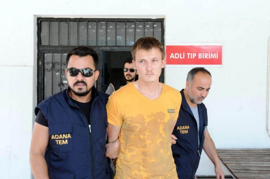 Russian national Renat Bakiev, a suspected Islamic State militant who allegedly planned to use a drone to bring down a U.S. plane at the Incirlik air base, is escorted by police officers as he arrives to a hospital for a medical check in the city of