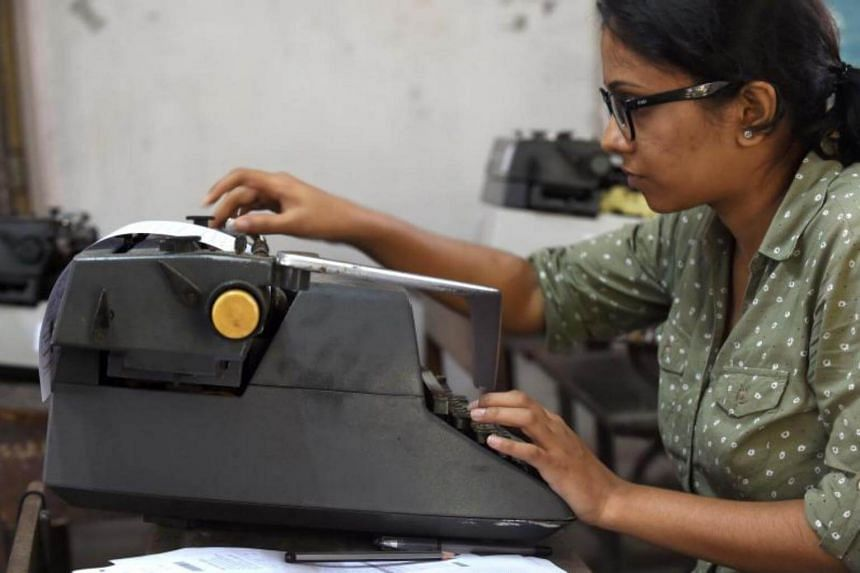 A candidate adjusts her answer sheet on a typewriter as she appears for the last official typing exam conducted by the state government in Mumbai.