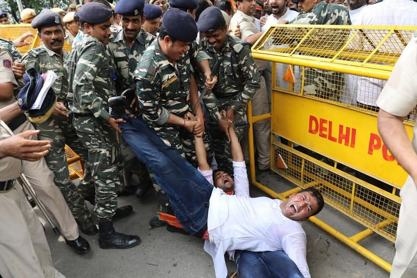 Indian Police personnel detain Indian Youth Congress activists during a protest against Bhartiya Janta Party (BJP) led Government in New Delhi, India on Aug 10, 2017.