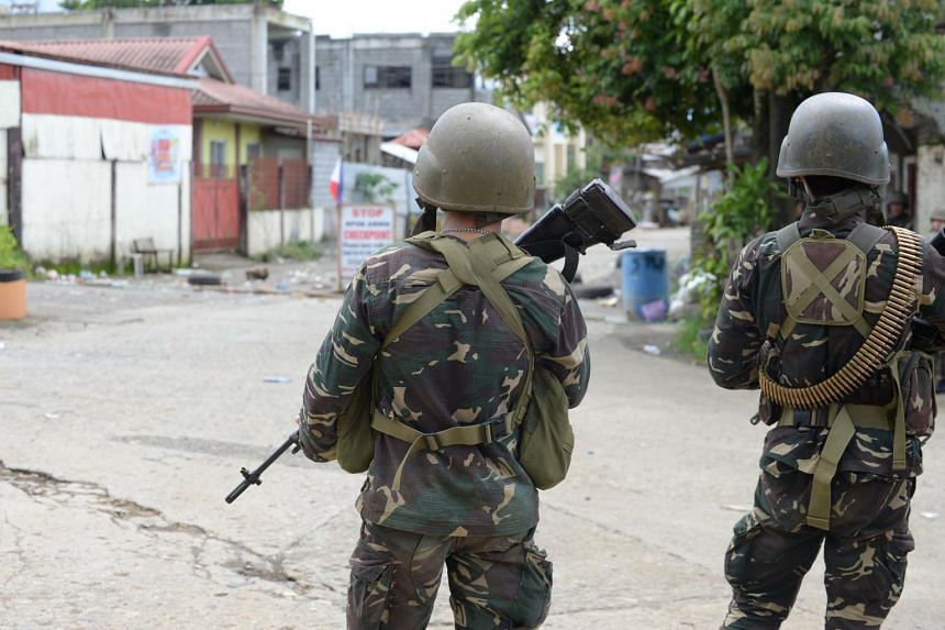 Philippine army troopers stand guard on a deserted street near the front line of the fighting between government troops and Muslim militants in Marawi, on June 25, 2017.
