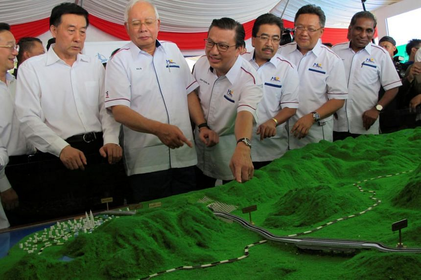 (From left) China State Councillor Wang Yong, Malaysian PM Najib Razak and Transport Minister Liow Tiong Lai looking at a model of the East Coast Rail Line, on Aug 9, 2017.