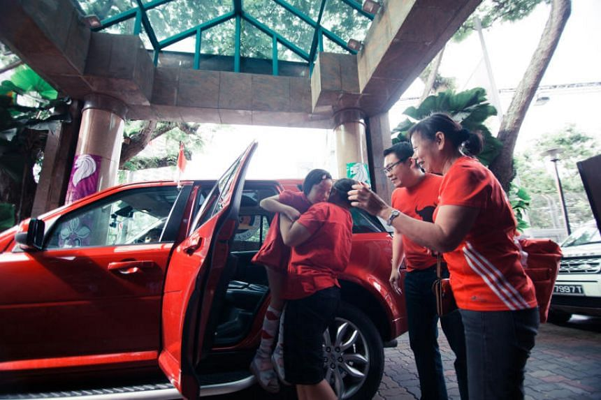 Rainbow Centre student alighting from a Land Rover at the Singapore Recreation Club on Aug 9, 2017, to watch a live screening of NDP, as part of the Charity Drive organised by Wearnes Automotive.