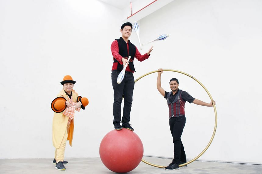 Mr Edward Chua (far left), who specialises in hat juggling, with Mr Benjamin Teo (centre), whose forte is juggling, and Mr Firdaus Ayoob Piperdy, the roue cyr (cyr wheel) specialist. Circus In Motion founder Jay Che, under whose guidance Mr Teo, Mr C