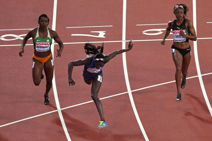 US athlete Tori Bowie (centre) crosses the finish line next to vory Coast's Murielle Ahoure (left) and Jamaica's Elaine Thompson to win the final of the women's 100m athletics event at the 2017 IAAF World Championships at the London Stadium in London