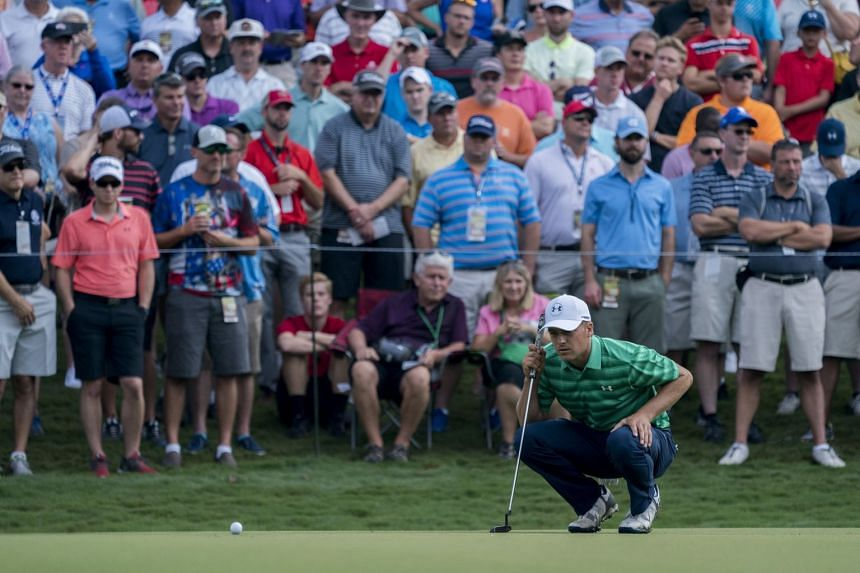 Spieth reads the green prior to putting on the 13th hole during the first round.