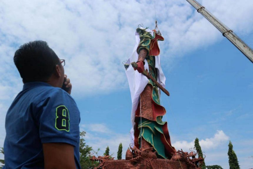 A crane is used to cover the statue of Guan Yu, a Chinese deity, with a cloth in Tuban.