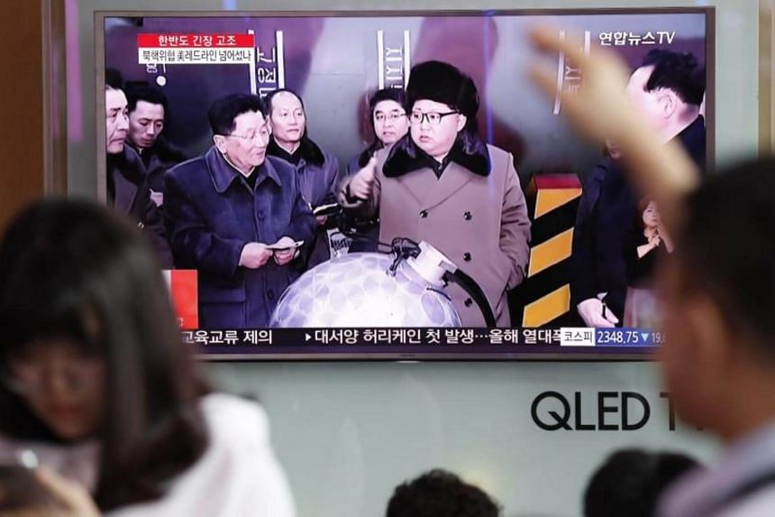 South Koreans watch a television displaying news broadcasts reporting on North Korea at a station in Seoul, on Aug 10, 2017.