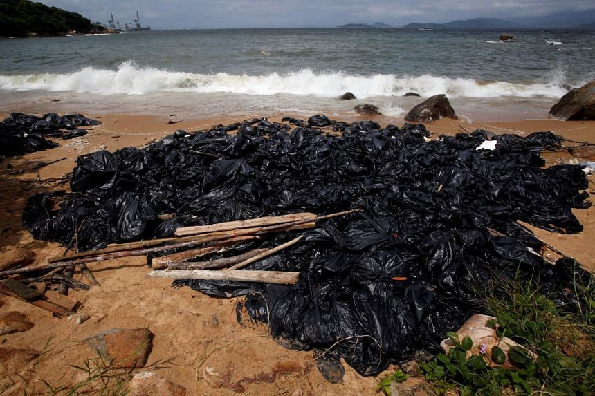 Garbage bags containing collected crystallised palm oil are seen on a beach at Lamma Island in Hong Kong, on Aug 9, 2017.