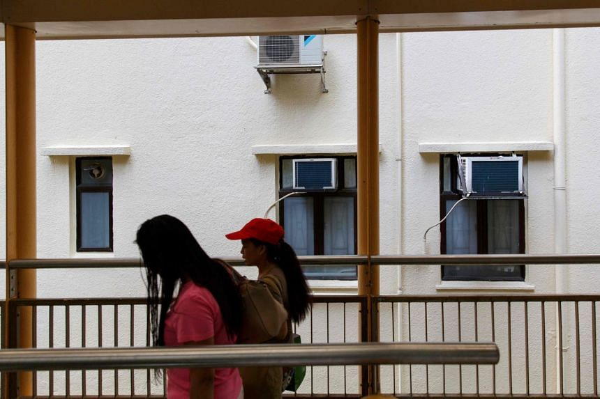 Migrant workers employed as domestic maids walk past air conditioning units of a residential apartment block in Hong Kong's Mid-Levels district on Aug 11, 2017.