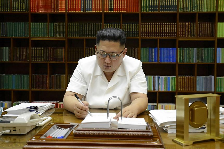 Kim Jong Un signing documents for the test launch of an intercontinental ballistic missile (ICBM), Hwasong-14, at an undisclosed place in North Korea.