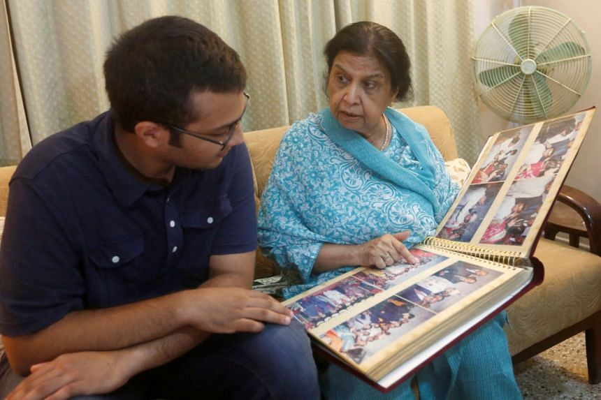 Rehana Khursheed Hashmi, 75, who migrated from India with her family in 1960 and whose relatives, live in India, speaks with her grandson Zain Hashmi, 19, while looking family photo album at her residence in Karachi, Pakistan.