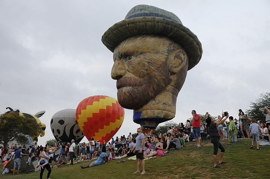 A hot-air balloon in the likeness of artist Vincent van Gogh hovering above spectators and participants at the International Hot Air Balloon Festival at Eshkol National Park in Northern Negev, Israel, yesterday. Israeli and international teams took p