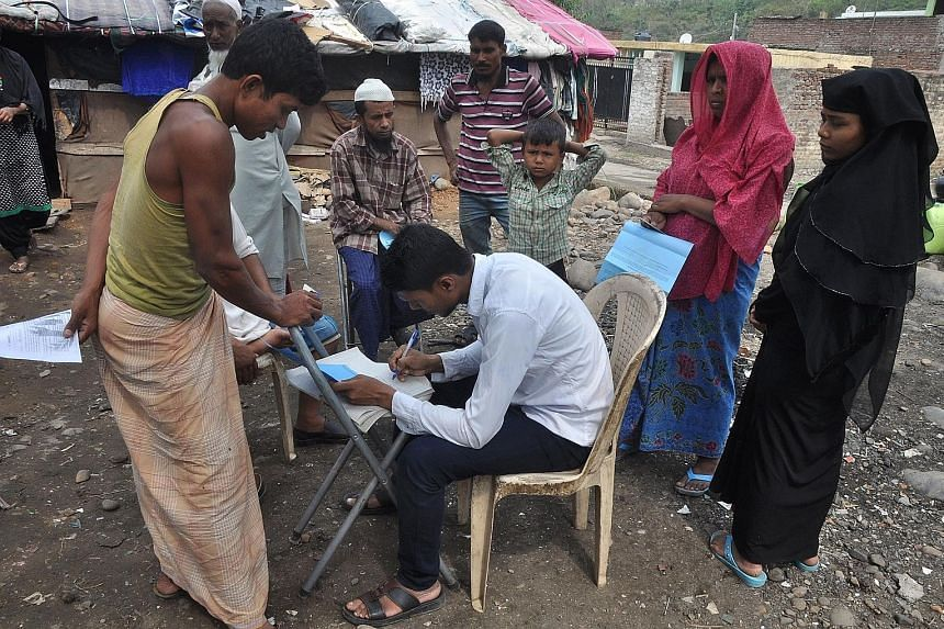 An aid worker with the United Nations High Commissioner for Refugees gathering details about the Rohingya Muslim refugees at a makeshift camp on the outskirts of the Indian city Jammu in June. New Delhi says only around 14,000 of the Rohingya living