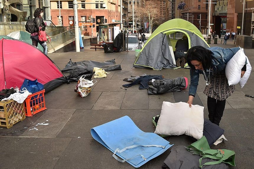 "A homeless woman packing up her belongings in Martin Place, which had become known as ""tent city"", in the central business district of Sydney yesterday. The camp had become the most visible symbol of the lack of low-cost accommodation in Sydney."