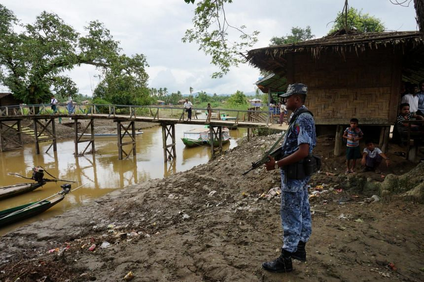 A Myanmar border guard police officer stands guard in Taung Bazar village, Buthidaung township, northern Rakhine state, Myanmar, on July 13, 2017.