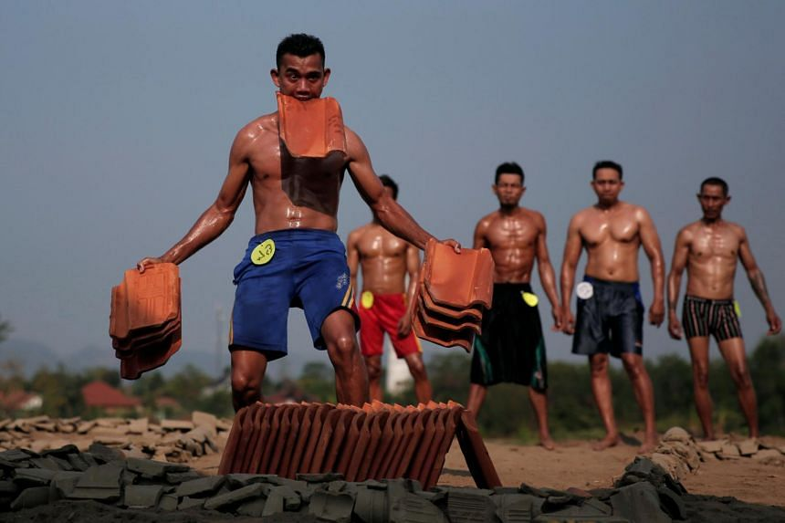 Workers take part in a bodybuilding contest for tile factory workers in Majalengka, West Java province, on Aug 11, 2017.