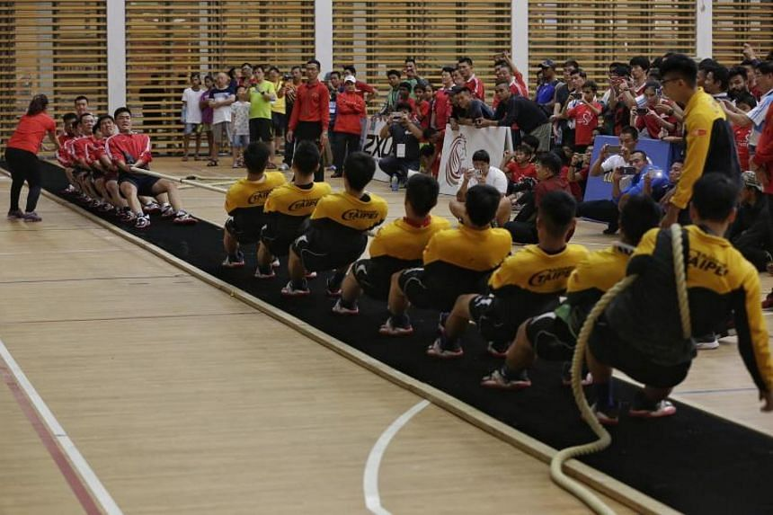 Taiwan's Tai-chung Tug of War (in yellow and black) and China's Ju Yong Guan Team 1 (in red) tug it out during the final of the Asian Tug of War Championships at Republic Polytechnic Sports Hall on Aug 12, 2017.