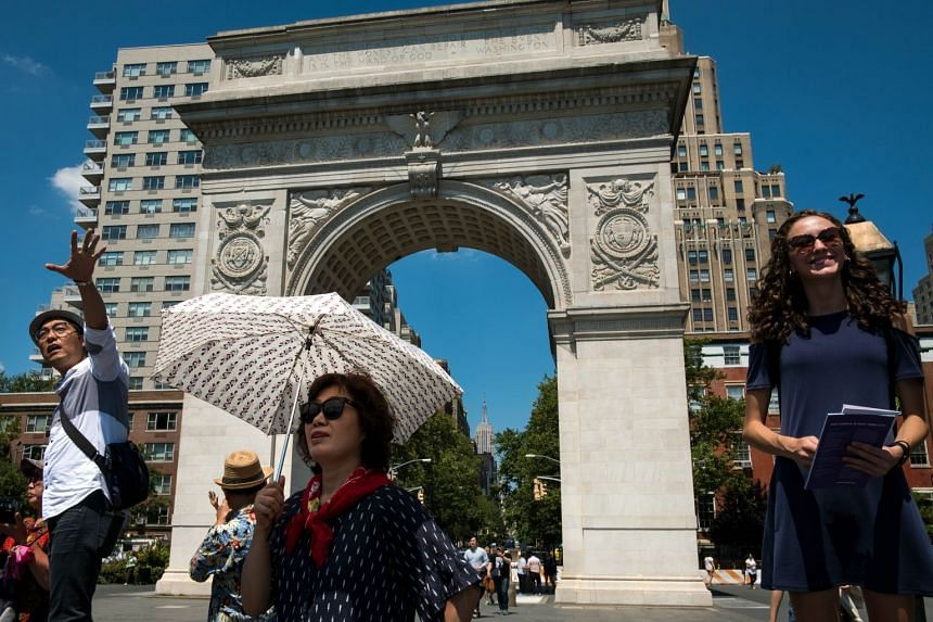 A tourist holds an umbrella to shield herself from the sun as she tours Washington Square Park, July 19, 2017, in New York City.