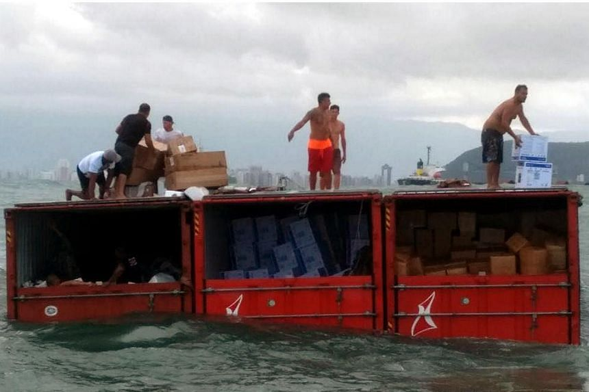 People looting containers that fell from the Brazilian cargo ship Log-In Pantanal, some 4km away from the coast of Santos on August 11, 2017.