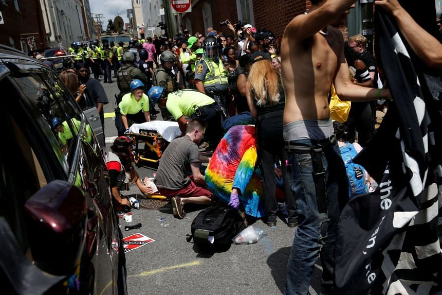Rescue workers assist people who were injured when a car drove through a group of counter protesters.