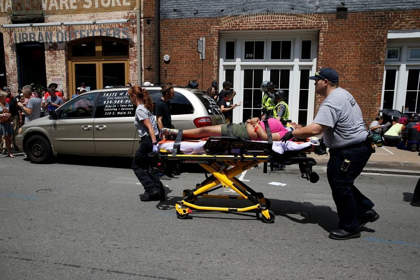 Rescue workers transport a victim who was injured when a car drove through a group of counter-protesters at the rally.
