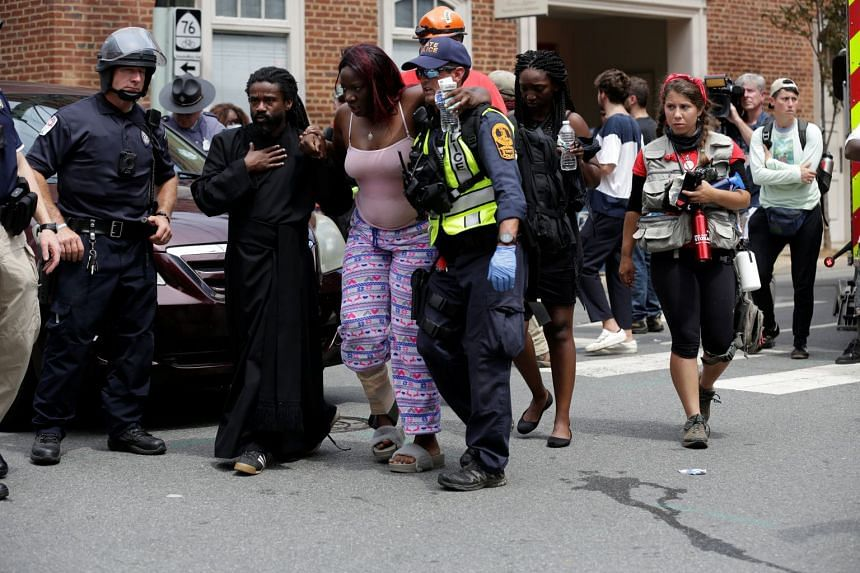 """Rescue workers assist a victim who was injured when a car drove through a group of counter-protesters at the """"Unite the Right"""" rally."""