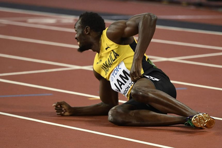 Usain Bolt of Jamaica reacts after sustaining an injury.